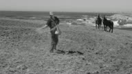 WS View of man sowing seed on ground with horse and ocean in distance
