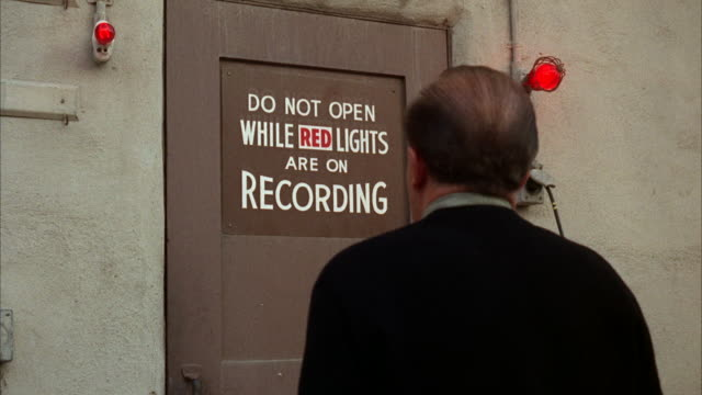 MS View of  man standing in front of studio sound stage with sign of DO NOT OPEN WHEN RED LIGHTS ARE ON