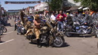 WS ZI ZO TS View of man wearing fur hat maneuvers his fur and antler covering motorcycle out of parking spot and rides away during Sturgis Motorcycle Rally / Sturgis, South Dakota, United States