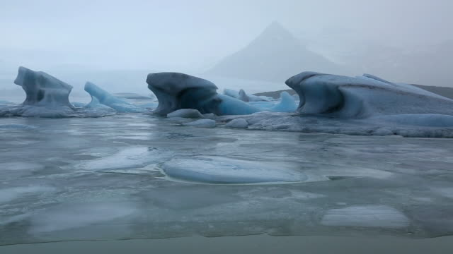MS PAN View of many glaciers floating and drifting on calm Fjallsarlon Glacier Lake at morning in raining / Iceland