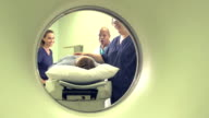 View of medical professionals, patient thru CT scanner