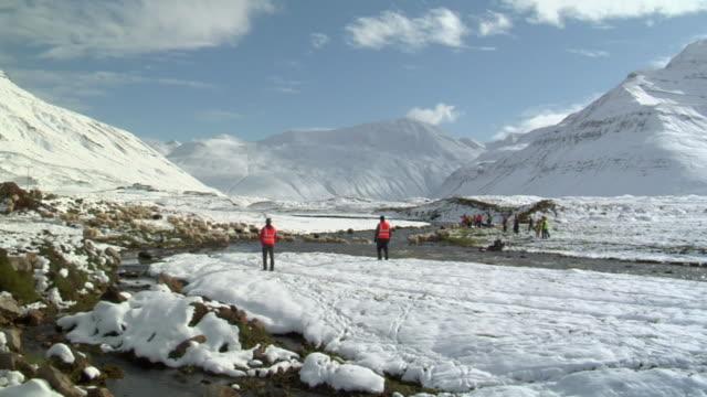 WS View of men in vests move Icelandic sheep through river during rettir / Skagafjorour, Nordhurland Vestra, Iceland