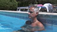 MS CU View of Men relaxing in swimming pool / Palma de Majorque, Majorque, Spain