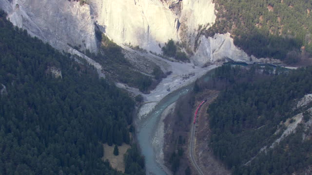 WS AERIAL View of MGB Train moving side by river / Switzerland