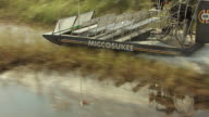 MS AERIAL TS View of Miccosukee Airboat moving on water in everglades / Florida, United States