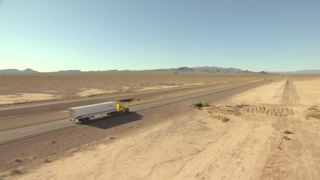 WS AERIAL View of Mojave Desert tracking semi truck on highway in flat desert valley with bright sunshine / Nevada, United States