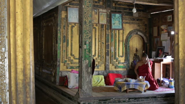WS View of Monk on phone in his office, taking notes / Inle Lake, Shan State, Myanmar