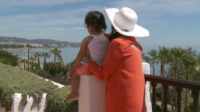MS View of mother and his little girl looking at city / Marbella, Andalusia, Spain