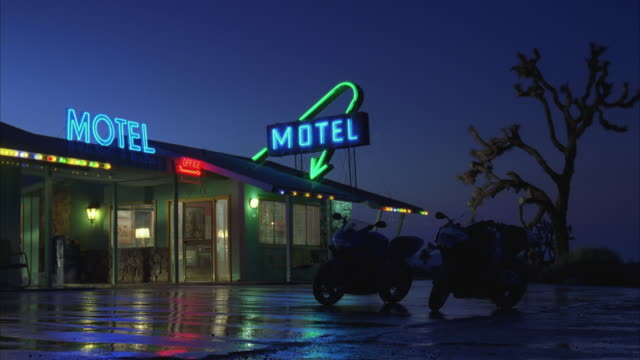 WS View of motorbikes parked in front of motel at night