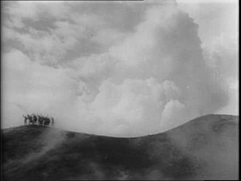 View of Mount Vesuvius smoking / American soldiers walking on hardened lava rock while Vesuvius produces smoke / lava flows with soldiers walking in...