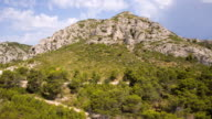 WS AERIAL View of mountain with wine yards and cars moving on road / St. Remy de Provence, Provence, France