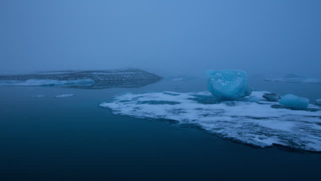 MS T/L PAN View of moving float glaciers on Jokulsarlon lake and bridge at early morning / Ireland