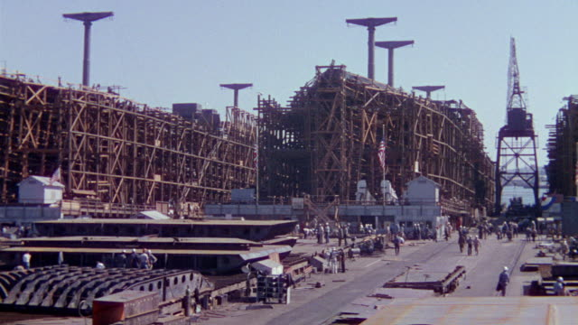WS PAN View of naval shipyard with construction going and Large ship