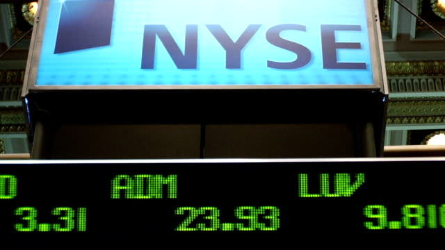 View of NYSE sign and ticker above trading floor of New York Stock Exchange New York City