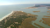 WS AERIAL View of ocean and Estuary with town at State border (inlet) / North Carolina, United States