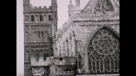 View of of Exeter Cathedral in the mid 1930s with period cars and people walking by the door / Filmed pre WW2 before the building was largely...
