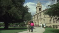 WS View of old school building with lawn in front and people walking on path