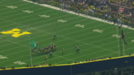 MS AERIAL ZO View of  orbit around Michigan Stadium and football players on field / Ann Arbor, Michigan, United States