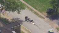 WS AERIAL View of orbit man being interviewed by camera crew at Canfield Drive where Michael Brown was killed with make shift street memorial in Ferguson / St Louis, Missouri, United States