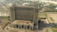WS AERIAL View of orbit Michigan Central Station with grown over tracks / Detroit, Michigan, United States