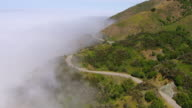 WS AERIAL View of Pacific Coast Highway snakes along side of mountain with dense fog / California, United States