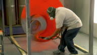 MS View of painter covers an art piece metal sculpture with orange colored powder coat / Cathedral City, California, USA