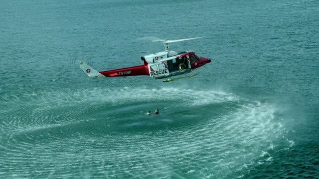 WS AERIAL ZI View of paramedic rescuing man in sea while rescue helicopter hovers above / Cape Town, Western Cape, South Africa