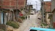 WS View of pedestrians and traffic on a dusty dirt street in Ciudad Bolivar slum / Bogota, Colombia