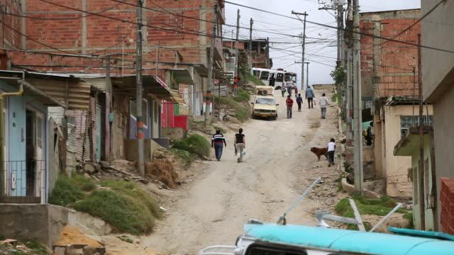 WS View of pedestrians and traffic on a dusty dirt street in Ciudad Bolivar slum / Bogota, Colombia