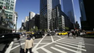 WS TU T/L View of People and cars crossing intersection with shadow of buildings growing and covering buildings / New York, USA