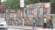 WS PAN View of People and traffic go by wall cover with paintings for sale/ Port-au-Prince, Haiti