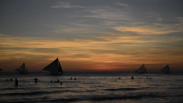 WS View of people enjoying in ocean at Sunset time on White Beach / Boracay, Philippines