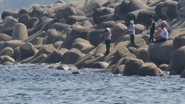 View of people fishing at waterbreak in Dongmyeong-port