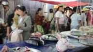 MS PAN View of People moving in front of fish and foods stall at Local Market and fish for sale / Nyaungshwe, Shan State, Myanmar