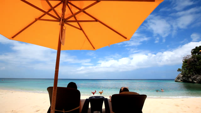 View of people resting on the patio chairs at the beach of Boracay Island