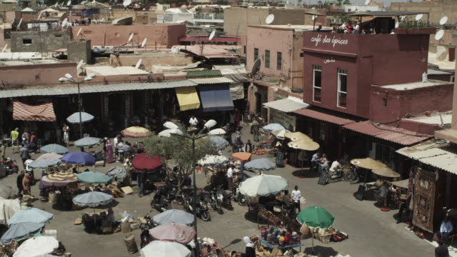 WS ZI View of people walking on street and market place with souk rooftops / Marrakesh, Morocco