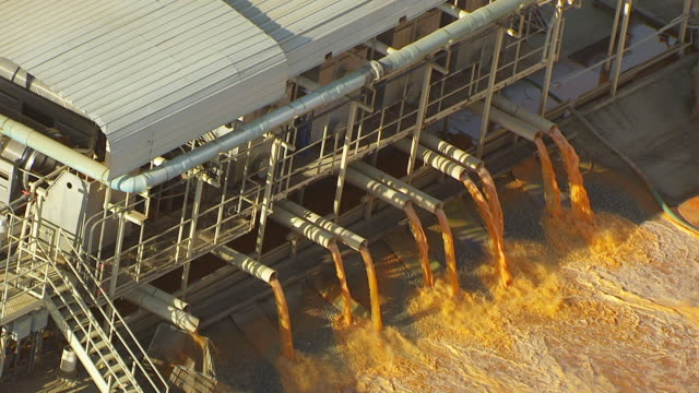 WS ZO AERIAL POV View of pipes dropping liquid into pool in Carrot Processing Plant / Bakersfield, California, United States