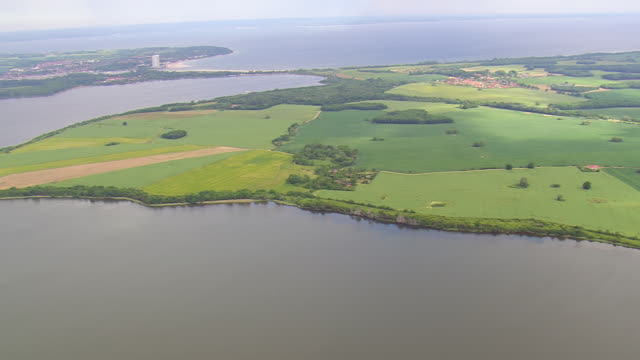 WS AERIAL View of Potenitzer wiek lake and ocean with houses and farm field / Germany
