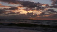 WS View of Purple and pink sunrise peeking through grey clouds over ocean / Aniston, Western Cape, South Africa