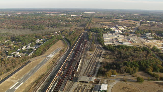 WS AERIAL View of railway tracks in city with wooded area / South Carolina, United States