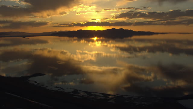 WS AERIAL View of reflection of blazing orange sunset on great salt lake / Utah, United States