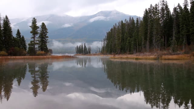 WS TU View of reflection on lake to clouds hanging over calm misty lake with evergreen trees and large mountains / Seeley Lake, Montana, United States