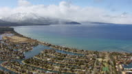 WS AERIAL POV View of residential area and marina with Lake Tahoe and snowcapped mountain in background in northern Sierra Nevada / South Lake Tahoe, California, United States