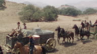 WS View of riders on horse back with carriage on dirt road