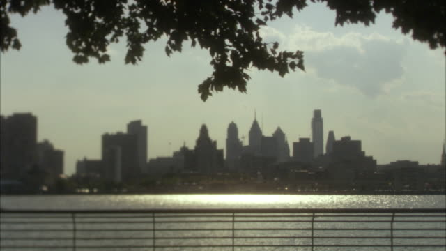 WS View of river at dusk with skylines in background / Philadelphia, Pennsylvania, USA