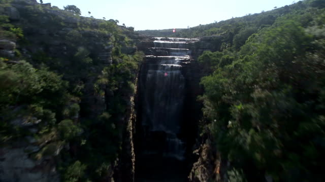 WS AERIAL View of river waterfall between tree covered cliffs / Kwazulu Natal, South Africa