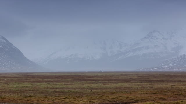WS PAN View of road going towards snow mountain through small lake / Iceland