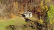 MS AERIAL DS View of Robert Frost Cabin surrounded by trees at Homer Noble Farm / Vermont, United States