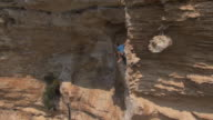 AERIAL view of rock climber scaling overhanging cliff