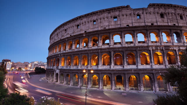 T/L View of Rome's Colosseum or Coliseum and urban traffic at susnet / Rome, Italy